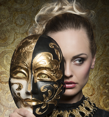 close-up carnival portrait of very beautiful blonde woman with baroque mask in the hands and antique precious jewellery