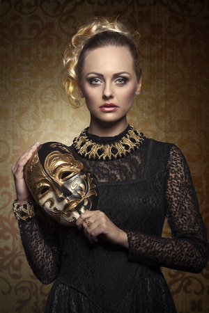 costume jewelry: carnival portrait of blonde woman with aristocratic antique lady mask, elegant lace dress and baroque jewellery. Venetian mask in the hand