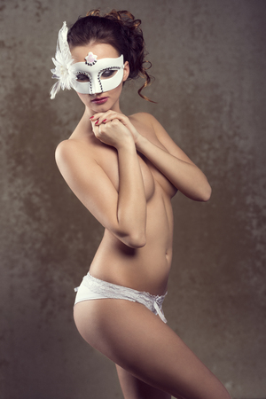 body mask: Beautiful, sexy, nude woman in white lingerie and white carnival mask with nice hairstyle and dark make up. Stock Photo