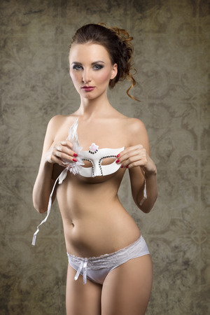 mysterious woman: Beautiful, charming, sexy, sensual, nude woman in white lingerie and white carnival mask with dark make up. Stock Photo