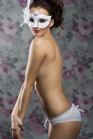 body mask: Beautiful, sexy fit woman in white lingerie and white carnival mask with nice hairstyle and smokey eye.