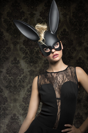 ear rings: Sexy, beautiful woman in black rabbit mask and back dress with perfect dark make up.