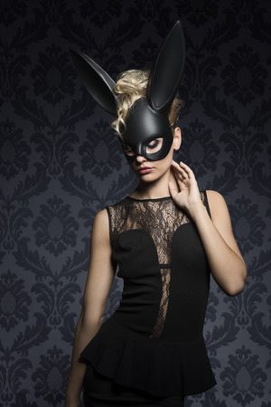 ear rings: Sexy, beautiful, charming, blonde woamn in black rabbit mask and elegant black dress. Stock Photo