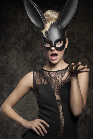sexy costume: Sexy, beautiful, charming woman in black dress and carnival black rabbit mask in funny pose.