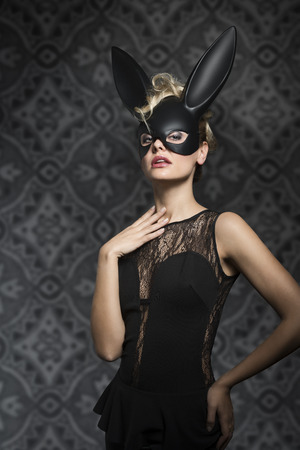 ear rings: Sexy, pretty, elegant blonde woman in black dress and rabbit mask with dark make up.