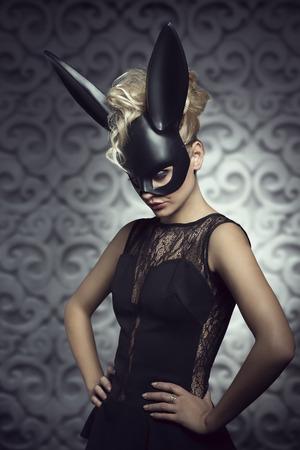Sexy, beau, chaud, femme blonde en robe noire élégante de noir masque de lapin et maquillage foncé.