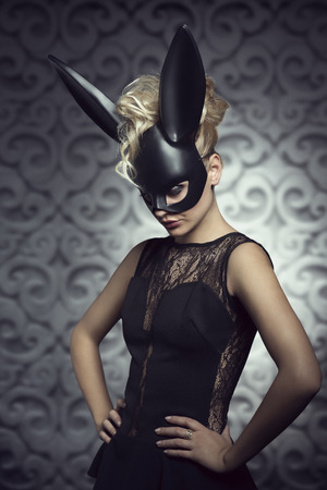 black mask: Sexy, beautiful, hot, blonde woman in elegant black dress with black rabbit mask and dark makeup.