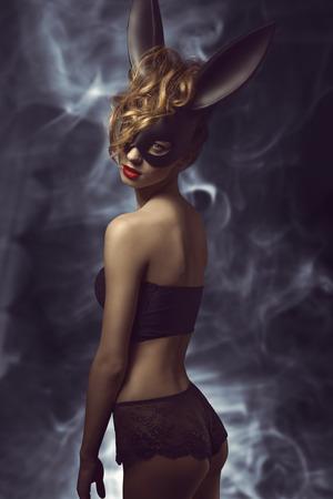 hacer el amor: Mujer rizada posando en Pascua glamour lanzamiento de la manera con negro extraña máscara de conejo y elegante ropa interior de encaje Foto de archivo