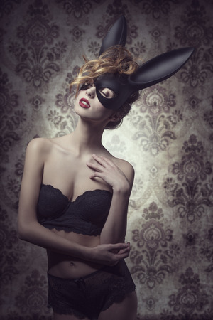 Dark easter portrait of sensual curly woman with romantic expression posing with mysterious bunny mask and lace lingerie 免版税图像