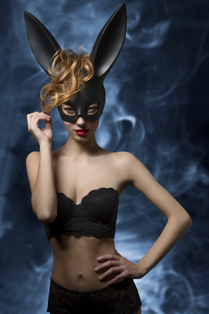 costumes: Provocative young woman with dark bunny ears posing in easter glamour portrait with lace lingerie and perfect body