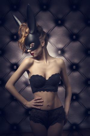 la mode glamour tournage de la femme mignonne au corps parfait dentelle lingerie sexy et bizarre masque de lapin noir. Sombre Pâques