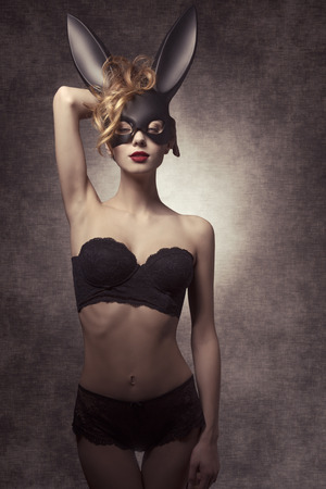 make love: Easter dark shoot of beautiful curly girl with glamour ace lingerie and bizarre bunny mask, in fashion pose