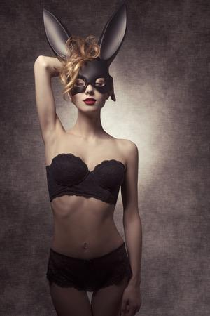 hacer el amor: Pascua disparar oscuro de la hermosa chica rizada con lencería as glamour y la máscara de conejito extraño, en actitud de la manera