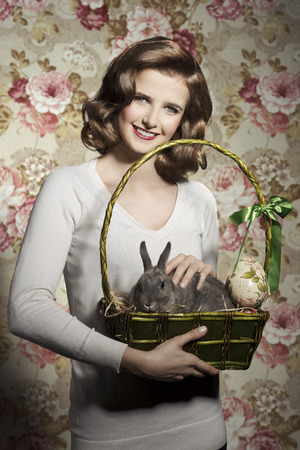 Beautiful, natural, sweet, cheerful, brunette woman is holding basket with fluffy rabbit and an egg.