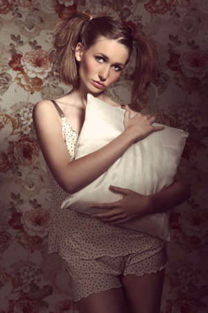 ponytails: Lovely, fresh, pretty woman has got nice ponytails and cute make up, wears beige pijamas and holding a pillow.
