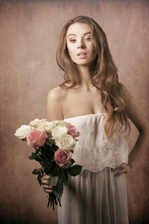 beuty of nature: Beautiful, young, charming, gorgeous girl with curly hairstyle and bouquet of roses. She wears white etno dress. Stock Photo