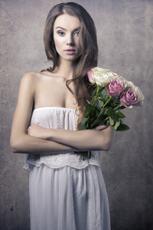 messy hair: Beautiful, romantic, natural, young girl with curly, messy hair and white long dress holding a bouquet of roses.