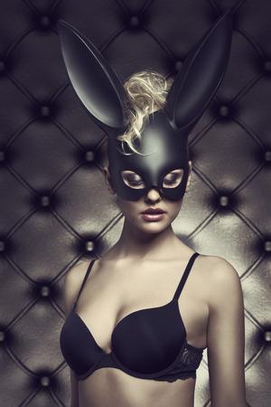 カーリーの髪のスタイルを黒バニー カーニバル マスクを持つセクシーなランジェリーでポーズをとってセクシーな金髪の女性。ゴシック様式のイー