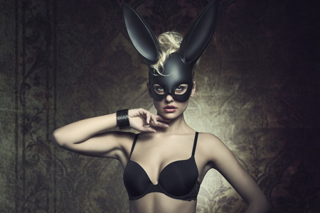 costumes: fashion Easter creative portrait of mysterious woman with blonde curly hair-style and lack bra posing with cute dark bunny mask. Fetish atmosphere Stock Photo
