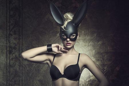 Pâques mode portrait créatif de femme mystérieuse avec des cheveux de style bouclés blonds et manquent de soutien-gorge posant avec mignon sombre masque de lapin. Atmosphère Fétiche Banque d'images