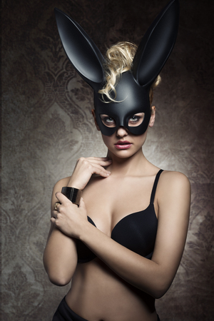 glamour easter portrait of charming blonde curly woman with dark lingerie and bizarre bunny masquerade. Dark atmosphere