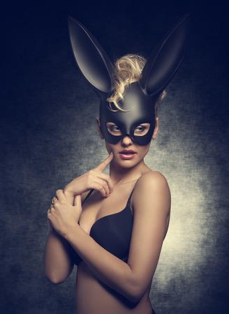 femme blonde sensuelle avec des cheveux bouclés style posant comme Playgirl avec soutien-gorge noir et bizarre masque de lapin sur le visage.