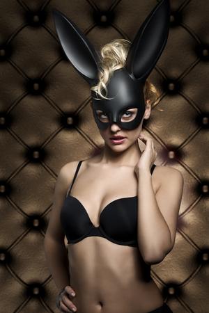 lapin sexy: pâques shoot glamour très sexy femme blonde avec les cheveux bouclés de style et de la lingerie noir, portant création élégant masque de lapin noir sur le visage et en regardant dans la caméra Banque d'images