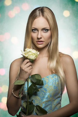 long silky hair: spring portrait of romantic blonde woman with long silky hair, wearing stylish dress and taking beautiful rose in the hand