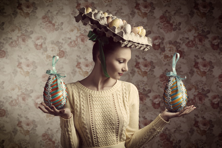 creative portrait of beautiful brunette woman with yellow clothes posing with easter eggs in carton box on the head. Bizarre hat, old fashion