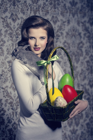 easter lovely portrait of brunette woman with retro hair-style posing with colorful eggs in cheerful basket and tender rabbit on her shoulder