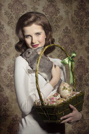 beautiful woman with vintage style taking in the hands easter eggs in cheerful basket and lovely tender rabbit