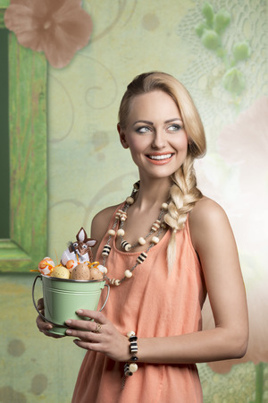 easter portrait of beautiful blonde woman with spring style and bucket with decorated easter eggs, she smiling photo