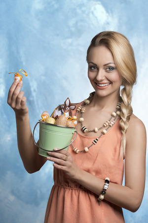happy blonde woman with braid hair-style and spring dress posing with some decorated easter eggs in small bucket, smiling and looking in camera