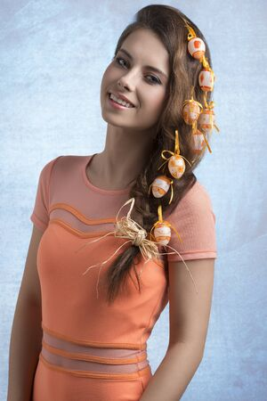 crazy hair: funny smiling brunette girl with easter crazy hair style with some colourful eggs in the hair, orange dress, spring style