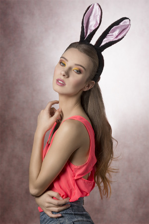 Pretty blonde, easter, natural girl with rabbit ears, nice outfit and yellow and brown make up.