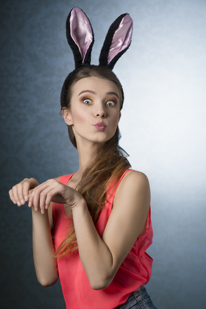 fluffy ears: Beautiful, natural, gorgeous, blonde woman with funny, fluffy rabbit ears on the head. She is posing like cute, little rabbit. Stock Photo