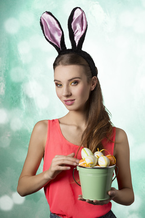 Pretty, happy blonde woman with long hair and rabbit ears on the head. She is holding bucket of little Easter eggs. photo