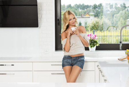 blond sexy woman in t-shirt and short , drinking from a cup , near a window kitchen in her luxury flat