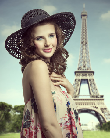 nautral: Bauttiful, nautral, stunning woman with curly brown hairstylea ans colorful make up. She is wearing colorful top with floral pattern and summer hat. Stock Photo