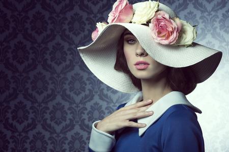 elegante mooie vrouw in blauwe jurk met een veer witte hoed, met roze en witte rozen over. Stockfoto
