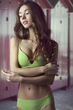 schattige brunette in een romantische pose met lang natuurlijk haar en zwembroek. Perfect lichaam