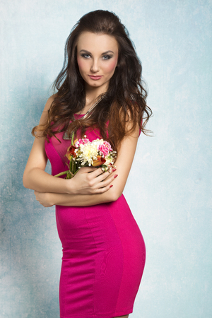 hair part: Pretty, natural, cheerful model with brown, curly, long hair. She wears pink dress with transparent part and nice silver necklace. She is holding bouquet of spring flowers.