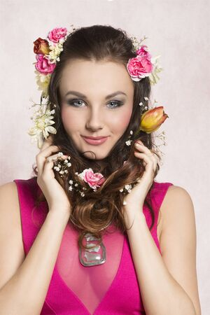 transparent dress: Pretty, natural, cheerful model with brown, curly hair with spring flowers. She wears pink dress with transparent part and nice silver necklace.