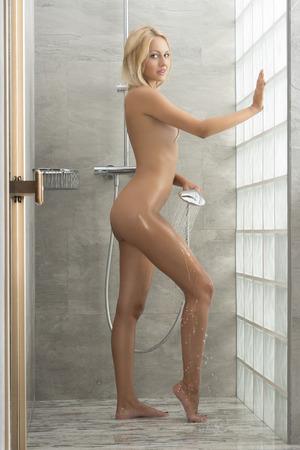mujer desnuda: Mujer sexy rubia en el ba�o. Ella est� bajo la ducha y ella est� salpicando su cuerpo con agua. Cuerpo desnudo perfecto Foto de archivo