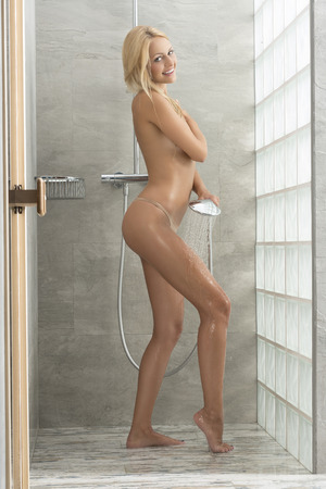 woman in shower: Natural, happy  young woman is in the bathroom under shower. She is splashing her body with water and smiling Stock Photo