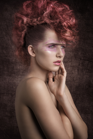 vamp: beauty shoot of stunning female with aggressive fashion style, rock red hairdo and punk creative make-up. Perfect skin, angelic expression
