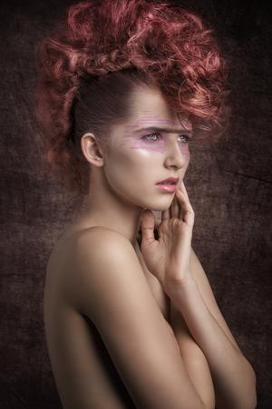cabello rojo: belleza brote de impresionante mujer con estilo de moda agresiva, peinado rojo rock y punk maquillaje creativo. Piel perfecta, expresi�n angelical Foto de archivo