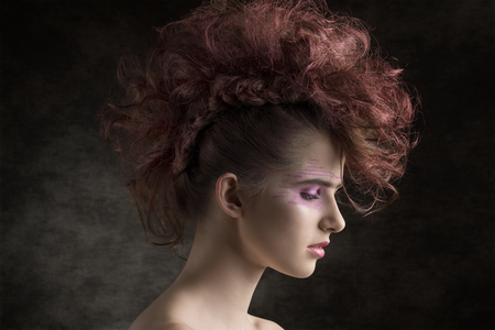 close-up beauty portrait of punk female with red rock hairdo and creative make-up. Perfect skin, aggressive fashion trendy style