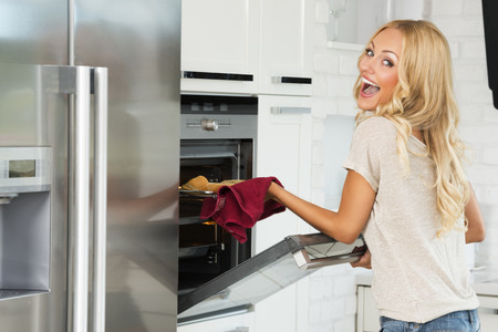 stove: very expressive commercial woman , with happy face , cooking some food with oven , in her kitchen.