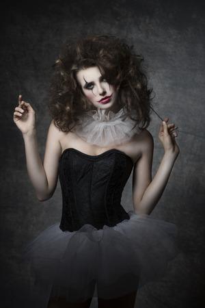 masquerade woman with vintage dancer dress, sad clown make-up and uncombed hair. Romantic fashion portrait Standard-Bild